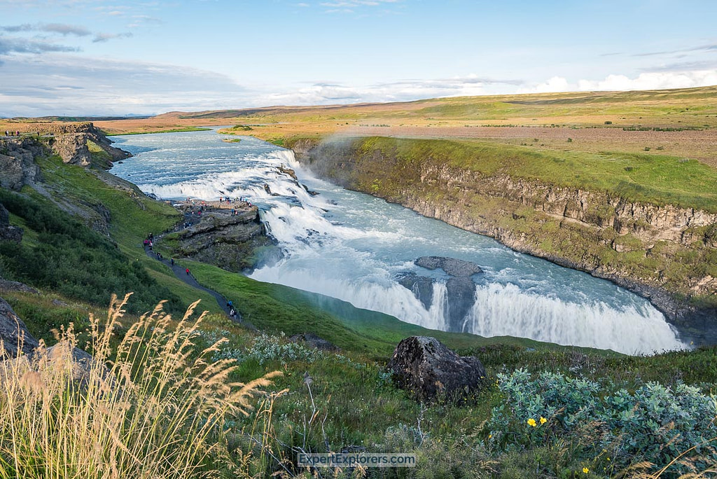 Colossal Gullfoss with tourists on the walking path approaching the waterfall, Iceland.