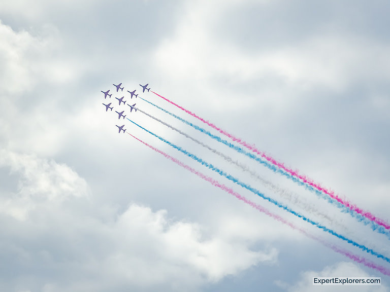 Nine of the UK's Red Arrow jets in formation streaming red white and blue smoke behind