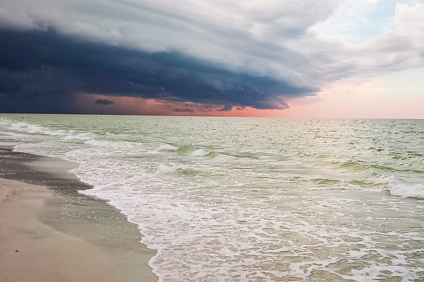 Storm clouds circle just before sunset on Redington Shores Beach in Florida