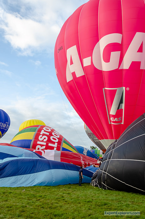 Man stands among giant hot air balloons being inflated at the Bristol International Balloon Fiesta
