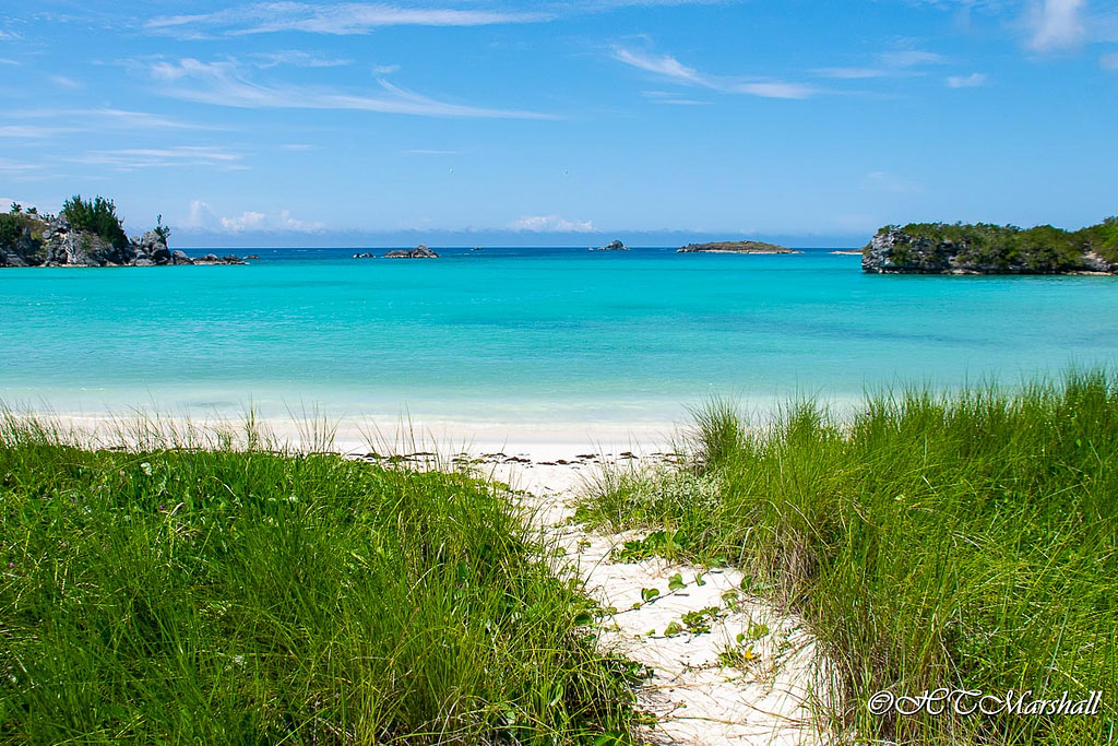 Path leads through grass to white sand and blue blue water of Well Bay in Coopers Island Bermuda