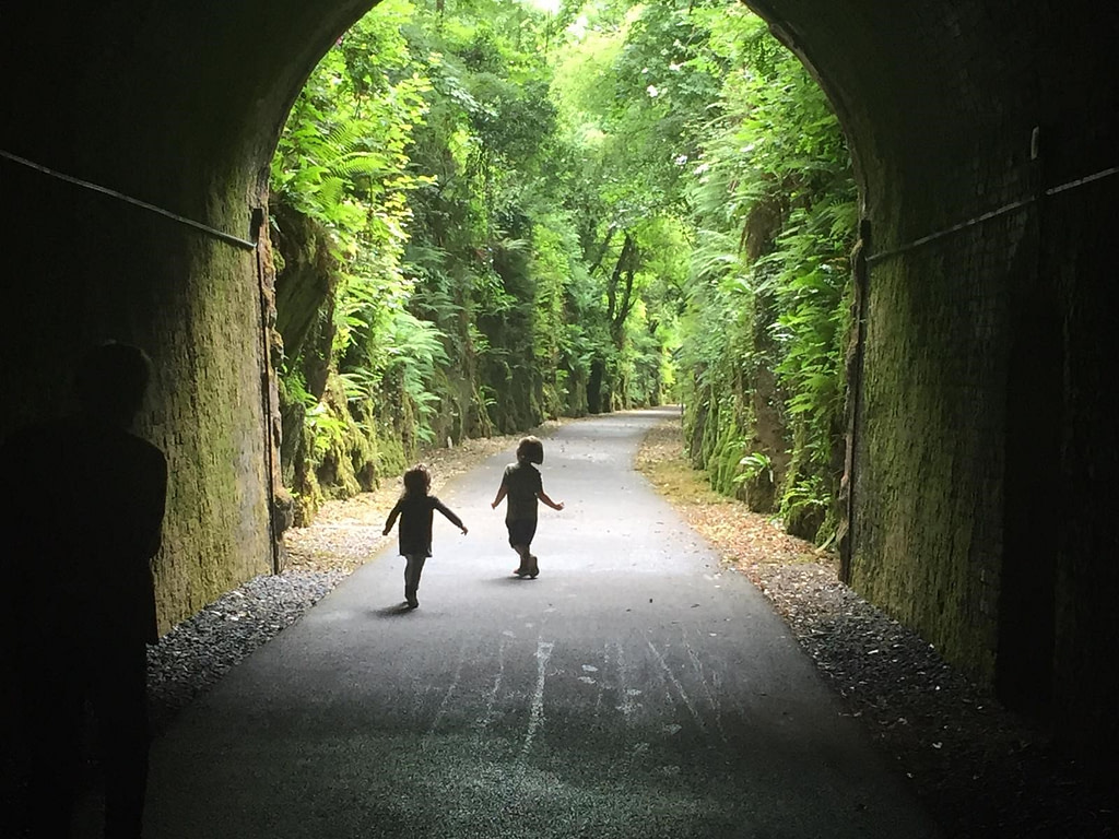 Two children skipping as they exit the Waterford Greenway tunnel, in Waterford, Ireland