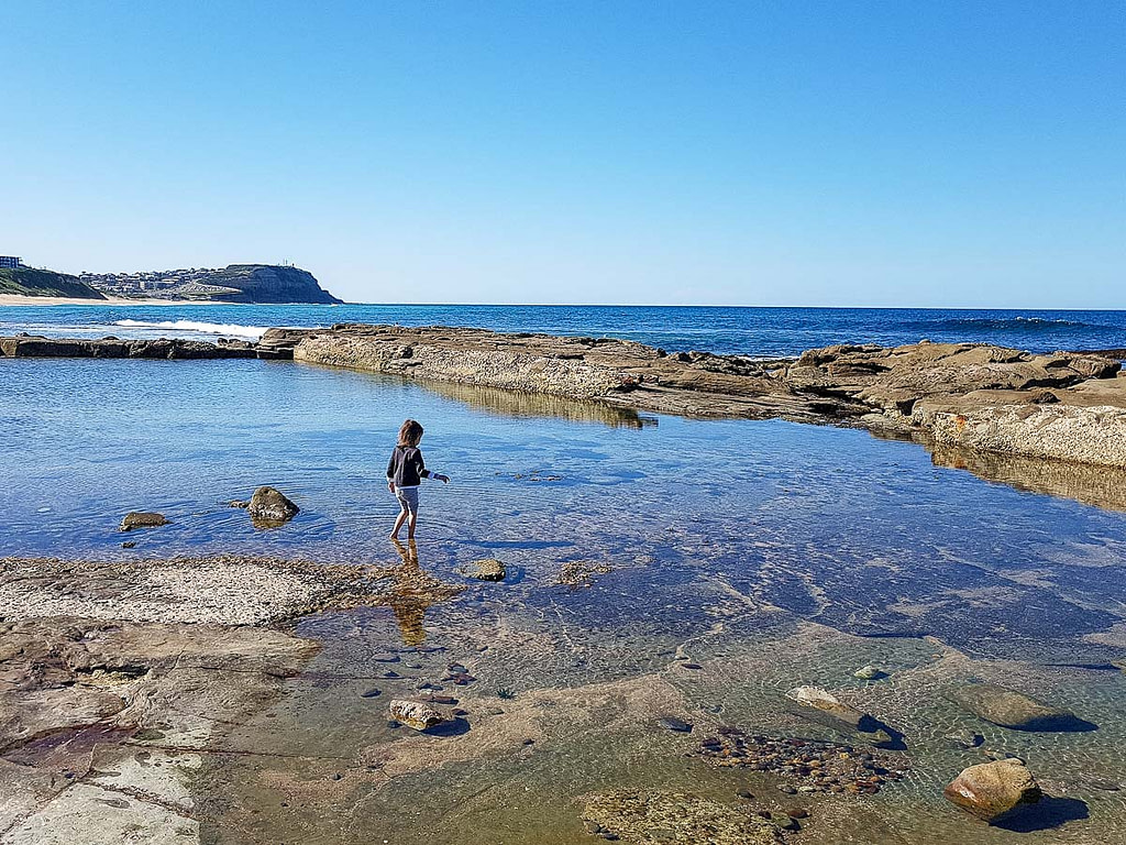 Young girl plays in the rock pool at Merewether Beach in Newcastle, Australia