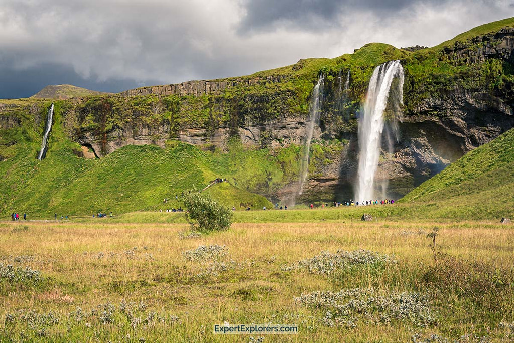Tourists walking up and through the ever popular Seljalandsfoss, Iceland Waterfalls, Iceland.