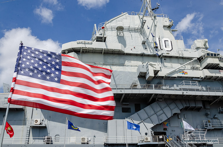 US flag waves in front of the USS Yorktown at Patriots Point