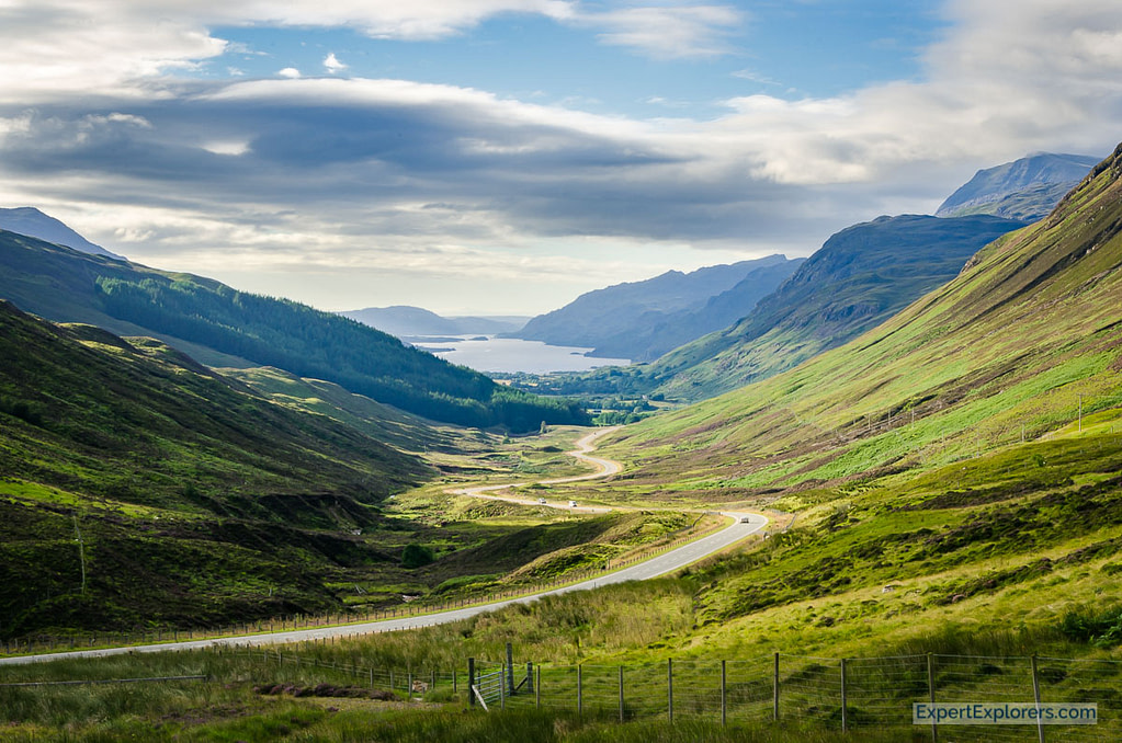 Road winds its way down to Loch Maree, with mountains on either side, seen from Glen Docherty view point, Scotland