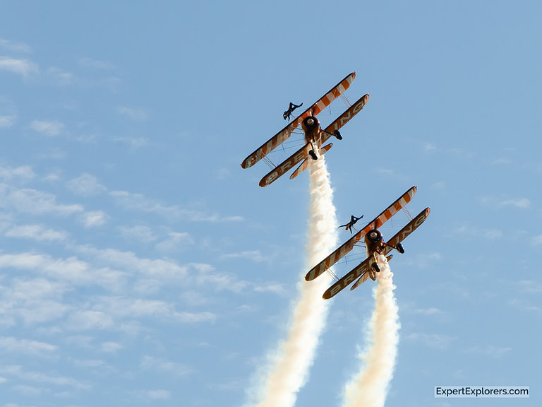 Two Breitling planes perform aeronautical tricks with women wing walkers on top