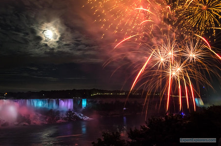 Fireworks and the moon light the night sky over Niagara Falls