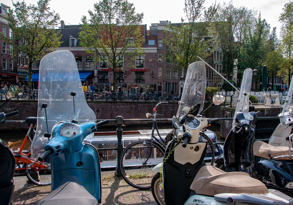 Moped, bikes, and a canal cruise show all the ways there are to get around in Amsterdam