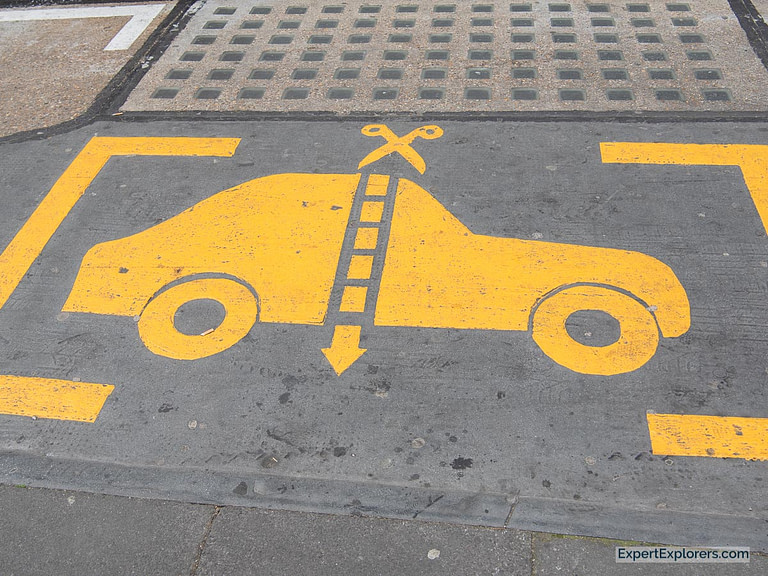 Street Art of Car being Cut in Half with Scissors in Parking Space