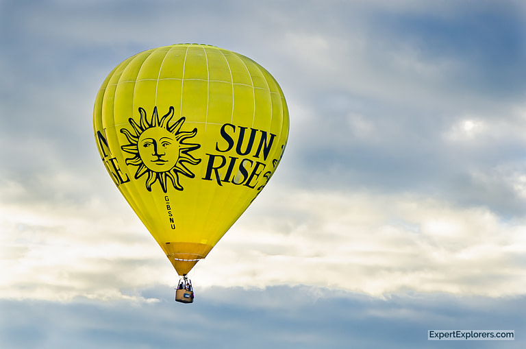 Large yellow Sun Rise hot air balloon floats among the clouds