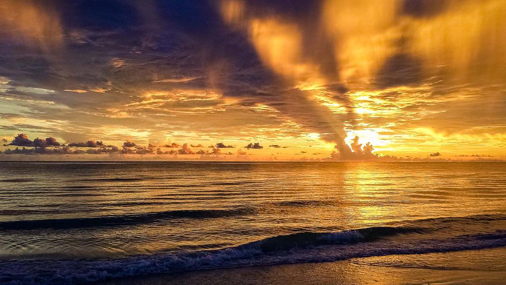 Clouds cut the vibrant yellow sunset sending beams of light through the sky at Redington Shores, Florida