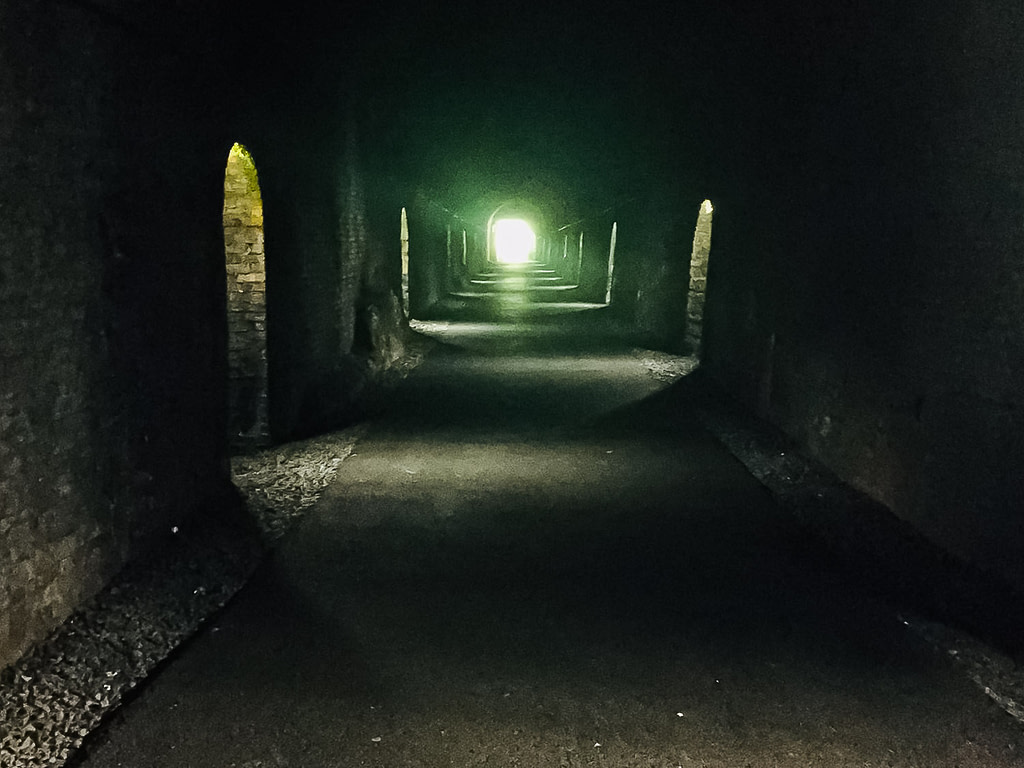 Long dark tunnel with light at the end on the Waterford Greenway, in Waterford Ireland