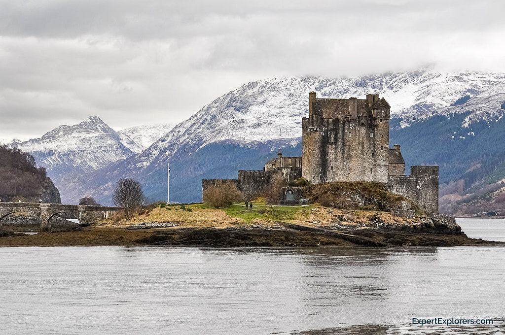 View of Eilean Donan Castle with Lochs in the foreground and snow topped mountains in the background, Scotland