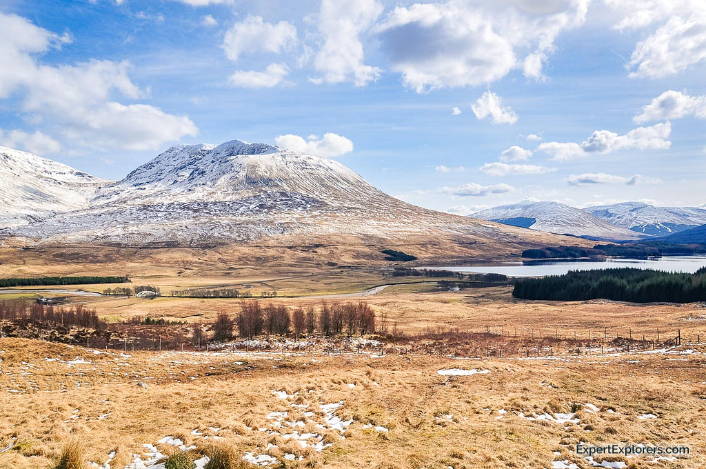 View of mountains partially covered in snow surrounding Loch Tulla, Scotland