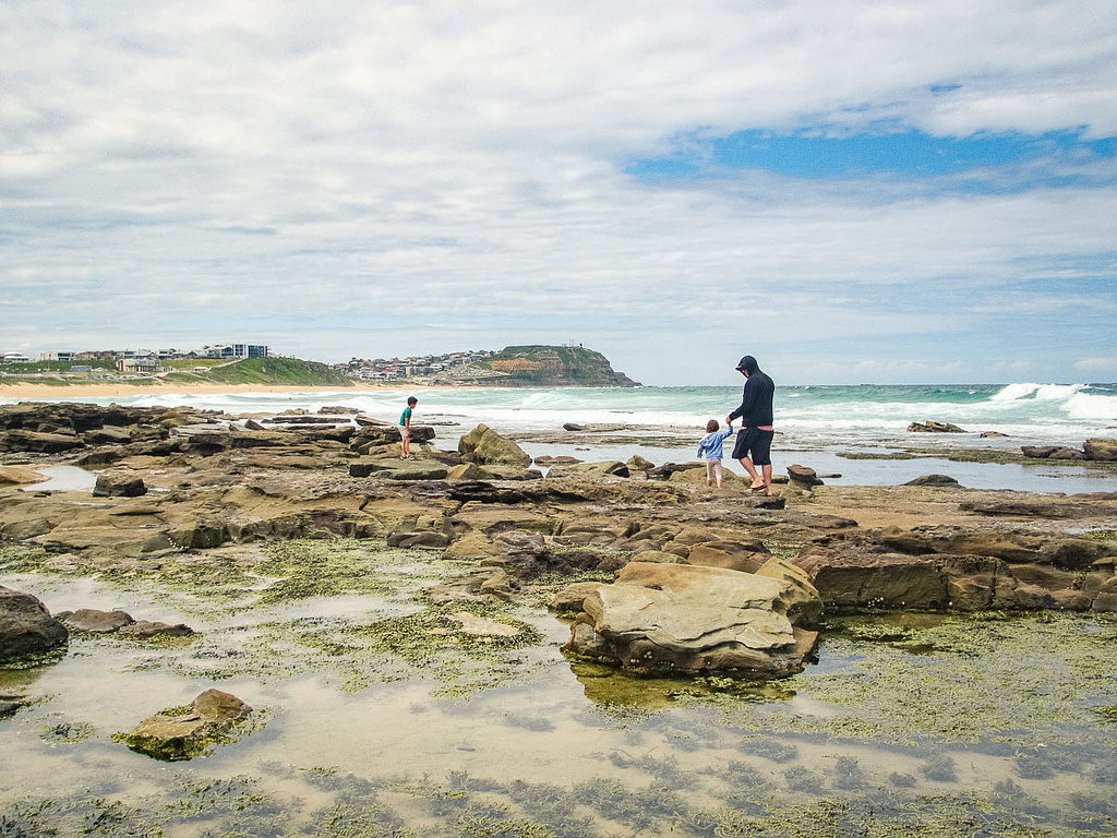 Children and man wonder along the rocks of Merewether Beach in Newcastle, Australia