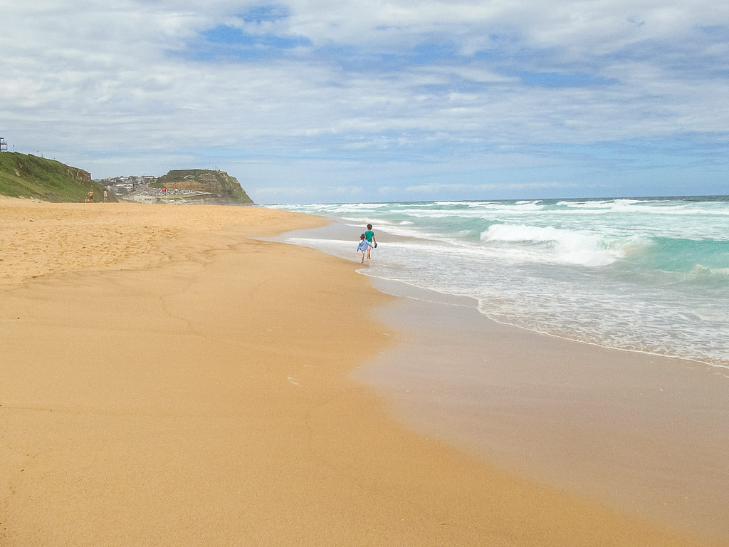 Children play near the ways of the empty Merewether Beach in Newcastle, Australia